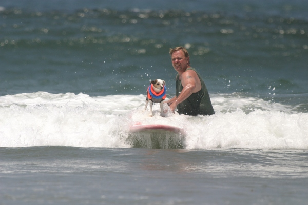 "Submitted by Vania:  ""A man helping his dog surf at the 3rd annual dog surfing competition in Imerial Beach, CA in 2008."""