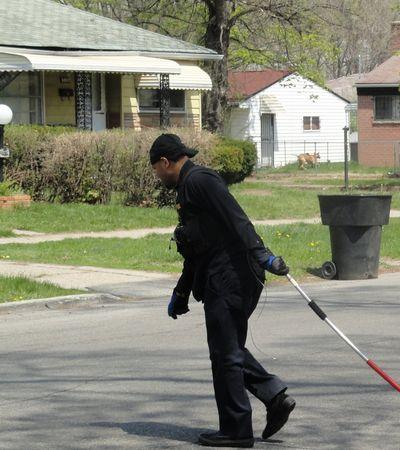 A Detroit ACO chokepoles a dog, possibly dead, across a street.  Screengrab from mlive.com.
